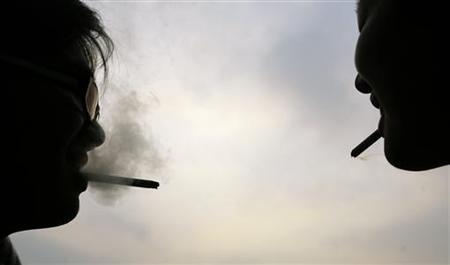 Two men smoke on a university campus in Pingtung County, southern Taiwan, January 13, 2010. REUTERS/Pichi Chuang