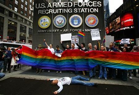Gay demonstrators and supporters hold a rainbow flag as one lays down on the sidewalk while they shout slogans during a protest at a U.S. Armed Forces Recruiting Station, in New York's Time's Square, March 15, 2007. REUTERS/Mike Segar