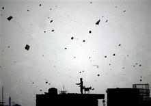 <p>A Pakistani kite-flyer is silhouetted against a sky filled with kites during Basant, an annual kite-flying festival, in Lahore March 12, 2006. REUTERS/Mohsin Raza</p>