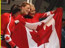 <p>Gold medalists Kaillie Humphries (R) and Heather Moyse (C) of Canada celebrate as teammate Helen Upperton (L) looks on after the final of women's bobsleigh at the Vancouver 2010 Winter Olympics in Whistler, British Columbia, February 24, 2010. REUTERS/Tony Gentile</p>