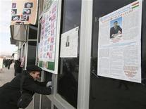 <p>Мужчина меняет валюту рядом с предвыборными плакатами в Душанбе 2 февраля 2010 года. Таджикистан в воскресенье избирает парламент, однако аналитики и избиратели уверены, что руководимая бессменным главой государства партия вновь получит контроль над законодательным органом. REUTERS/Nozim Kalandarov</p>