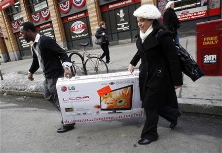 A woman and a sales clerk carry a large screen television to a waiting taxi in New York, February 18, 2010. REUTERS/Natalie Behring
