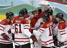 <p>Canada's hockey team celebrate after defeating Slovakia in their men's ice hockey playoff semifinals game at the Vancouver 2010 Winter Olympics February 26, 2010. REUTERS/Shaun Best</p>