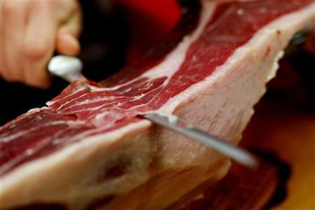 A stallholder cuts a slice from a leg of Spanish ham during Lo Mejor de La Gastronomia (The best of gastronomy), an international culinary trade fair in San Sebastian, November 21 2007. REUTERS/Vincent West