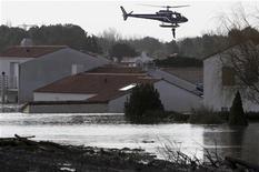 <p>Un abitante di La-Faute-sur-Mer viene tratto in salvo da un elicottero dopo un'inondazione, Francia, 28 febbraio 2010. REUTERS/Stephane Mahe</p>