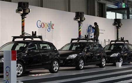 A worker makes final touches at the stand of Google where cars used for ''Google View'' are on display at the CeBIT exhibition centre in Hanover March 1, 2010. REUTERS/Fabrizio Bensch