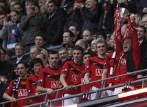 """<p>Игрок """"Манчестер Юнайтед"""" Уэйн Руни держит трофей после победы над """"Астон Виллой"""" в Кубке Лиги в Лондоне 28 февраля 2010 года. Группа британских финансистов хочет выкупить футбольный клуб """"Манчестер Юнайтед"""" за 1 миллиард фунтов стерлингов ($1,5 миллиарда), однако нынешние владельцы """"МЮ"""" не заинтересованы в продаже, сообщают британские СМИ. REUTERS/Darren Staples</p>"""
