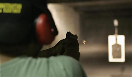 Jesse LaFlores fires a small .22 calibre handgun at Rink's Gun and Sport in the Chicago suburb of Lockport, June 26, 2008. REUTERS/Frank Polich