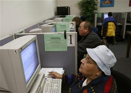 Ester Dela Cruz, laid off nine months ago from her job as an elderly care worker, searches for employment at a jobs center in San Francisco, California in this February 4, 2010 file photo. REUTERS/Robert Galbraith/Files
