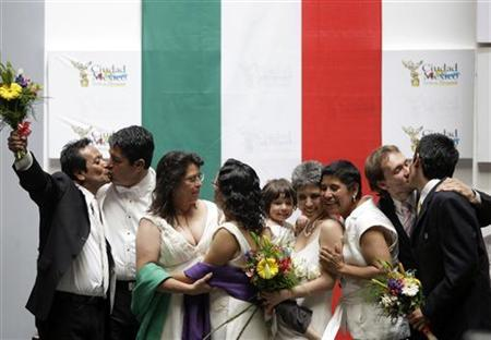 Four same-sex couples celebrate after getting married at the town hall in Mexico City in this March 11, 2010 file photo. REUTERS/Daniel Aguilar