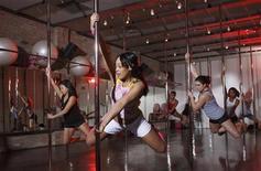 <p>Женщины участвуют на занятиях по стрип-пластике в фитнес-клубе в Чикаго 17 февраля 2009 года. Молодые женщины показывают стриптиз и танцуют у шеста на групповых занятиях фитнесом, которые помогают как работе их сердечно- сосудистой системы, так и делают их уверенными в себе. REUTERS/John Gress</p>
