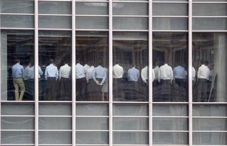 Staff are seen standing in a meeting room at the Lehman Brothers offices in London's Canary Wharf, September 11, 2008. REUTERS/Kevin Coombs
