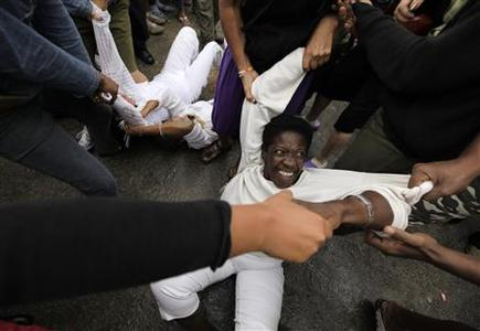 Security forces drag members of the Ladies in White, a group made up of family members of imprisoned dissidents, into a bus after a march in Havana March 17, 2010. REUTERS/Desmond Boylan