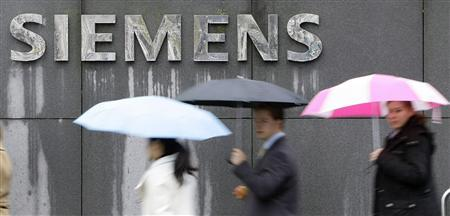 File picture shows people covered with umbrellas walking next to a Siemens building in Munich November 13, 2008. REUTERS/Michaela Rehle/File