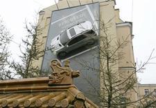 <p>Автомобиль, прикрепленный к рекламному щиту на здании в Санкт-Петербурге, 19 ноября 2006 года. Московские власти внесли в Госдуму законопроект, повышающий штрафы за неправильную парковку для российских водителей в 5-10 раз, говорится на сайте парламента РФ. REUTERS/Alexander Demianchuk</p>