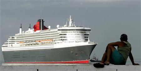 A man watches the Queen Mary 2 cruise ship during its arrival in Salvador's port, in the state of Bahia, in northeastern Brazil, February 19, 2004. REUTERS/Paulo Whitaker