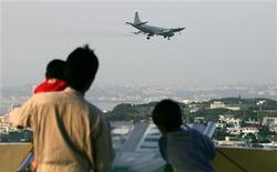 <p>A plane approaches to land at the U.S. Futenma air base as a family look on, in Ginowan, southern island of Okinawa March 31, 2006. REUTERS/Issei Kato</p>