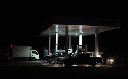 Drivers load gasoline at a local gas-station during a blackout in Santiago, March 14, 2010. REUTERS/Ivan Alvarado