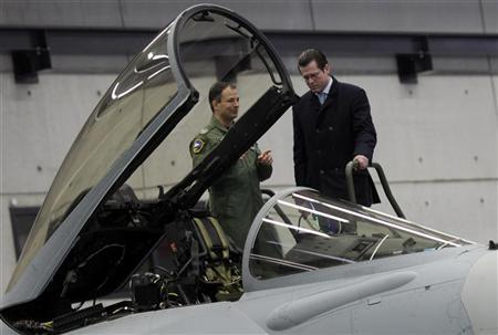 German Defence Minister Karl-Theodor zu Guttenberg looks at a Eurofighter jet plane during his visit at the Bundeswehr Fighter Squadron 74 in Neuburg January 11, 2010. REUTERS/Michael Dalder