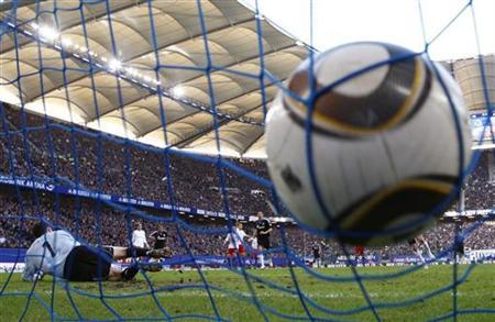 Schalke 04's Ivan Rakitic (covered) scores with a penalty against Hamburg SV's goalkeeper Frank Rost during their German Bundesliga first division soccer match in Hamburg March 21, 2010. REUTERS/Christian Charisius
