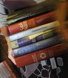 """<p>Работник книжного магазина в Лондоне держит книги, попавшие в """"шорт-лист"""" Букеровской премии 2009 года, 5 октября 2009 года. Четыре уже умерших писателя попали в список из шести авторов, претендующих на получение Букеровской премии за книги, написанные 40 лет назад. REUTERS/Toby Melville</p>"""