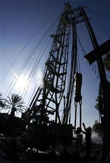 Workers drill for oil at an oil derrick in Los Angeles October 24, 2006. REUTERS/Lucy Nicholson