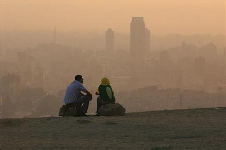 An Egyptian couple chat at the top of a mountain area that looks over Cairo during a smoggy day July 12, 2008 REUTERS/Asmaa Waguih