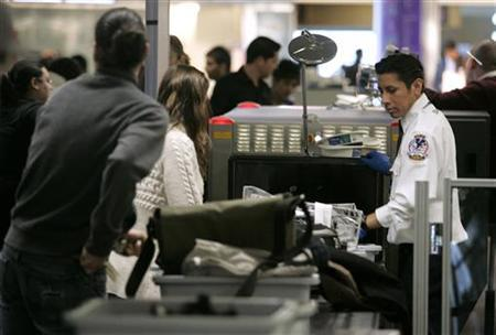 A U.S. Transportation Security Administration (TSA) agent looks at the baggages of airline passengers at a security checkpoint at San Francisco International Airport in California December 29, 2009. REUTERS/Robert Galbraith