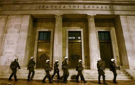 Riot policemen walk in front of the Bank of Greece during a rally against austerity measures in Athens March 16, 2010. REUTERS/John Kolesidis