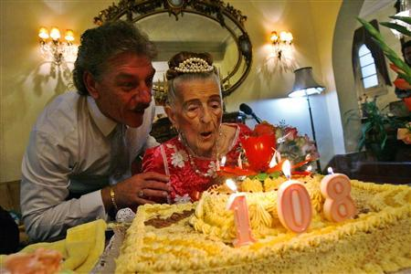 Mary McCarthy blows out the candles on her birthday cake with the help of her godson Elio Garcia at their home in Havana in this April 27, 2008 file photo. REUTERS/Claudia Daut/Files