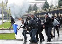 <p>Люди несут человека, пострадавшего во время беспорядков в Бишкеке, 7 апреля 2010 года. Сторонники киргизской оппозиции штурмуют здание правительства в Бишкеке, парализованном беспорядками после утреннего столкновения активистов с милицией и битвы со столичным спецназом в небольшом городе Талас накануне. REUTERS/Vladimir Pirogov</p>