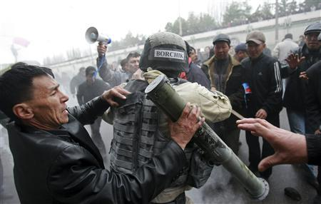 Protesters try to take a rocket propelled grenade (RPG) from a riot policeman during clashes in Bishkek, April 7, 2010. REUTERS/Vladimir Pirogov
