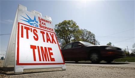 A car passes a sign advertising tax return services in Falls Church, Virginia, April 8, 2010. REUTERS/Kevin Lamarque