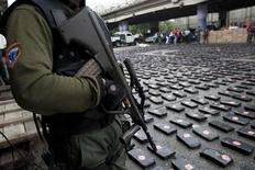 <p>Офицер полиции охраняет пачки наркотиков в Каракасе, 6 ноября 2009 года. Полиция Эквадора арестовала во вторник крупнейшего колумбийского наркобарона Рамона Кинтеро, экстрадиции которого добиваются США, сообщили власти в Боготе. REUTERS/Carlos Garcia</p>