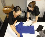 <p>Corie Chung (L), Marketing Director of Equmen, and Lynda Guthiere take measures on a sample t-shirt on Equmen Headquarters in Sydney April 14, 2010. REUTERS/Daniel Munoz</p>