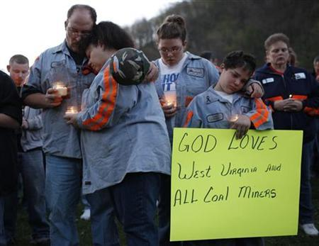 (L-R) Terry Cooper, his wife Michele, daughter Tera, 16, and son Justin, 11, comfort each other during a candlelight vigil in Montcoal, West Virginia April 10, 2010. REUTERS/John Gress