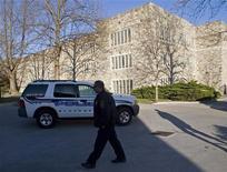 <p>Полицейский проходит перед зданием Виргинского политехнического института в Блэксбурге, штат Виргиния, 16 апреля 2007 года. Южно-корейский студент застрелил 32 человека в Виргинском политехническом институте, после чего покончил жизнь самоубийством. REUTERS/Chris Keane</p>