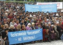 <p>Сторонники свергнутого президента Киризии Курманбека Бакиева на митинге в центре Джалалабада 13 апреля 2010 года. Сторонники свергнутого президента Киргизии Курманбека Бакиева захватили здание администрации города Джалалабад на юге страны. REUTERS/Denis Sinyakov</p>