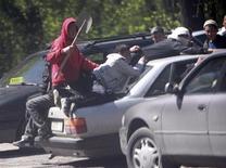 <p>Автомобиль с участниками беспорядков на крыше едеть по улице в селе Маевка недалеко от Бишкека 19 апреля 2010 года. AСамопровозглашенное правительство Киргизии пытается узаконить свою власть, предлагая политические реформы, однако не может совладать с сопротивлением сторонников свергнутого президента на юге страны, протестами милиции и вылазками мародеров, что грозит новой волной насилия. REUTERS/Vladimir Pirogov</p>