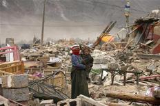 <p>Женщина с ребенком стоит посреди развалин дома в пострадавшем от сильного землетрясения районе Юйшу, КНР 19 апреля 2010 года. Число жертв землетрясения на западе Китае достигло 2.039 человек, среда в стране объявлена днем траура, сообщили власти. REUTERS/Donald Chan</p>