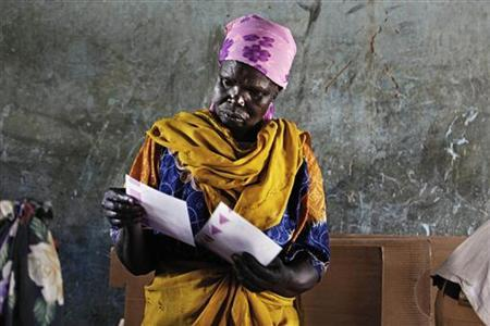 A Sudanese woman examines two of the twelve ballot papers cast by voters at a polling station in the town of Malakal in Upper Nile state, April 11, 2010. REUTERS/Finbarr O'Reilly