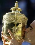 <p>Роджер Федерер целует уимблдонский кубок после победы над Энди Роддиком в Лондоне 5 июля 2009 года. Победители Уимблдона в одиночном разряде в 2010 году станут не только триумфаторами на самом известном теннисном турнире, но и получат в качестве призовой суммы по 1 миллиону фунтов стерлингов ($1,53 миллиона), сообщили во вторник организаторы. REUTERS/Stefan Wermuth</p>
