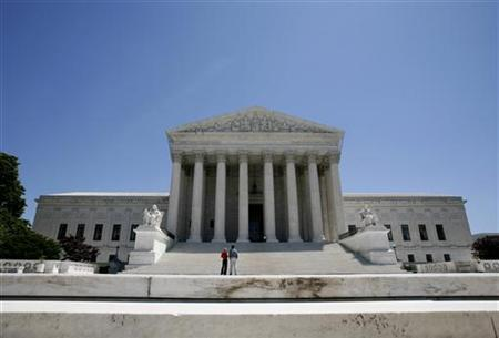 People stand at the foot of the steps of the Supreme Court in Washington, May 20, 2009. REUTERS/Molly Riley