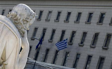 A Greek flag at the Bank of Greece is seen near a statue of ancient philosopher Socrates in Athens February 5, 2010. REUTERS/Yiorgos Karahalis