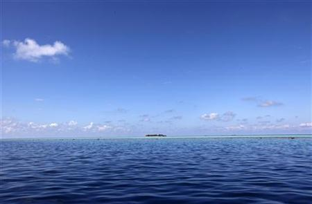 Clouds move over a resort island at the Male Atoll December 8, 2009. REUTERS/Reinhard Krause