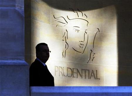A security guard is silhouetted in front a Prudential office in London, March 1, 2010. REUTERS/Luke MacGregor