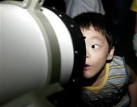 <p>Четырехлетний мальчик Сунго Танака смотрит в телескоп в Кавасаки, Япония 27 августа 2003 года. Самый большой телескоп в мире стоимостью более $1 миллиарда будет построен в Чили, что поможет ученым в поиске миров, похожих на наш, сообщила Южноевропейская обсерватория. REUTERS/Yuriko Nakao</p>