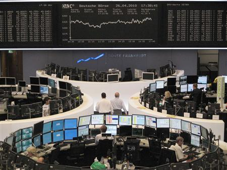 Traders are pictured at their desks in front of the DAX board at the Frankfurt stock exchange April 26, 2010. REUTERS/Remote/Amanda Andersen