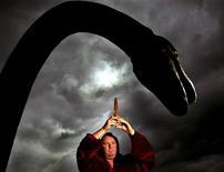 <p>Белый маг Кевин Карлион стоит около статуи Лохнесского чудовища на берегу озера и пытается вызвать монстра из воды 13 июня 2003 года. В 1930-е годы шотландская полиция не только не сомневалась в существовании Лохнесского чудовища, но даже собиралась защищать доисторического монстра от охотников. REUTERS/Jeff J Mitchell UK</p>