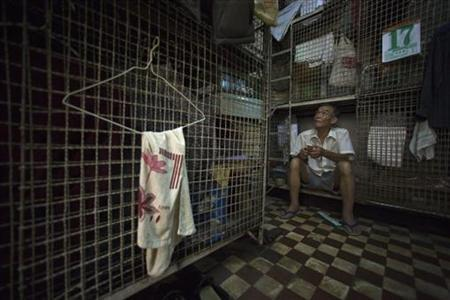 Kong Siu-kau waits for dinner in a small cage in Hong Kong's Tai Kok Tsui district July 16, 2008. REUTERS/Victor Fraile